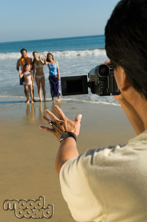 Man filming family on beach