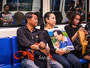 29 OCTOBER 2016 - BANGKOK, THAILAND:  Mourners on a Bangkok subway carry a portrait of the late Thai King. Saturday was the first day Thais could pay homage to the funeral urn of the late Bhumibol Adulyadej, King of Thailand, at Dusit Maha Prasart Throne Hall in the Grand Palace. The Palace said 10,000 people per day would be issued free tickerts to enter the Throne Hall but by late Saturday morning more than 100,000 people were in line and the palace scrapped plans to require mourners to get the free tickets. Traditionally, Thai Kings lay in state in their urns, but King Bhumibol Adulyadej is breaking with tradition. His urn reportedly contains some of his hair, but the King is in a coffin,  not in the urn. The laying in state will continue until at least January 2017 but may be extended.      PHOTO BY JACK KURTZ