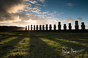 Sunrise over carved statues known as Moai at Ahu Tongariki on Easter Island, Chile.