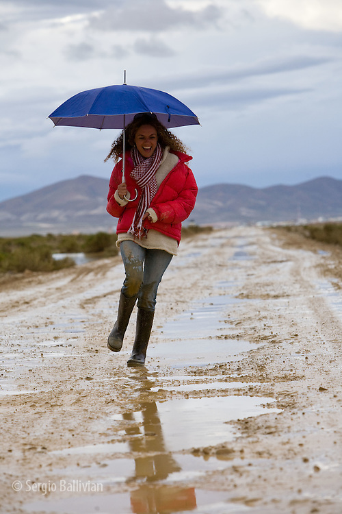A woman walks in the rain with an umbrella as the rainy season is well underway on the Altiplano near the city of Uyuni, Bolivia.