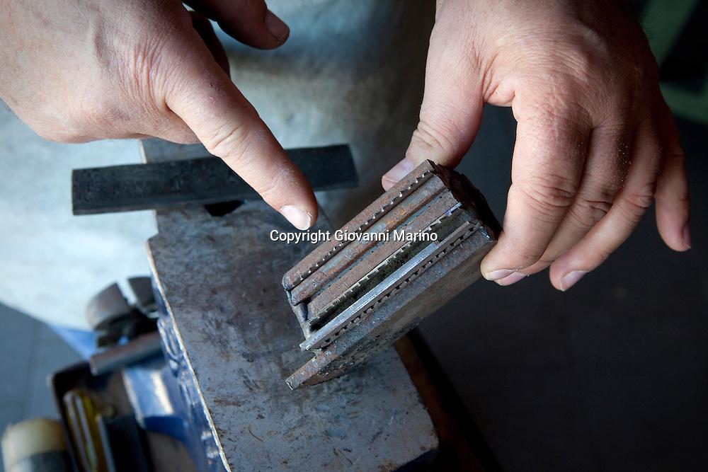 """Avigliano (PZ), 04-10-2010 ITALY - Vito Aquila, artigiano di Balestre. Il coltello di Avigliano, comunemente conosciuto come """"balestra"""", impreziosito con decorazioni in argento e ottone che le conferivano un certo valore non solo artistico,ha identificato per tutto l'Ottocento e parte del Novecento il carattere fiero e risoluto del popolo aviglianese, come attestato in una lunga casistica di riscontri documentari. La """"balestra"""" è un'arma a tutti gli effetti, ed è già considerata -nell'ambito delle manifatture di ferro - oggetto di pregio. Per l'approvvigionamento dell'argento e dell'ottone destinati alla decorazione del manico del coltello gli armieri si rivolgevano agli orefici o agli ottonari. La """"balestra"""" era un'arma del popolo, pronta ad essere impiegata, a seconda delle circostanze, per la difesa o l'offesa tanto dagli uomini quanto dalle donne. Queste, la ricevevano come regalo di fidanzamento dal rispettivo promesso sposo per meglio difendere il proprio onore, perpetrando un'usanza molto sentita almeno fino ai primi decenni del '900..Nella Foto: Pezzi di ferro che verranno fusi ed utilizzati per forgiare la balestra."""