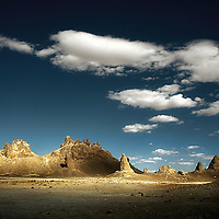 Distant view with strange rock formations under a blue sky with white clouds