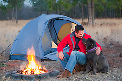 Man in a red jacket sitting bside a campfire with his dog out in South Carolina