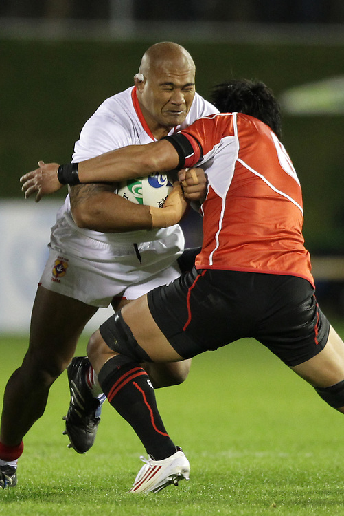 Tonga's Alisona Taumalolo is tackled by Japan's Takashi Kikutani during a Pool A match of the Rugby World Cup 2011, Northland Events Centre, Whangarei, New Zealand, Wednesday, September 21, 2011.  Credit:SNPA / David Rowland