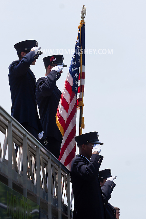 Monroe, New York - Members of the Mombasha Fire Company salute as the  procession carrying Army Capt. Jason B. Jones passes by on Route 17 on the from Pennsylvania to funeral services at  West Point on June 17, 2014.  Jones was killed in Afghanistan on June 2, 2014.