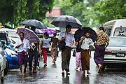 "12 JUNE 2013 - YANGON, MYANMAR:   Men wearing ""longyis,"" a traditional Burmese garment, walk through a rainy season thunderstorm in Yangon, Myanmar.       PHOTO BY JACK KURTZ"