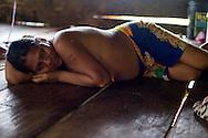 Mujer Embera acostada en el piso de su choza. Comunidad indígena La Chunga, Comarca Embera – Wounaan en la Provincia de Darién, Panamá.  La Chuga, ubicada en el  Rio Sambu, forma parte del corredor biológico de Bagres con sus inmensos bosques tropicales.