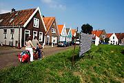 Twee mensen fietsen op de tandem voorbij de drogende was in Durgerdam.<br /> <br /> Two cyclists are passing Durgerdam by tandem.