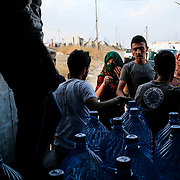 DOHUK, IRAQ - OCTOBER 24: A water distribution truck makes its rounds at Badarash IDPs camp which has continued to swell for Syrian Kurdish refugees fleeing the recent Turkish incursion in Rojava. In seven days UNHCR reports that 7,100 have now arrived on October 24, 2019 in Dohuk, Iraq. Many fleeing have said saying they paid to be smuggled through the Syrian border.  (Photo by Byron Smith/Getty Images)