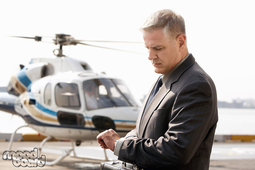Businessman waiting at helicopter pad
