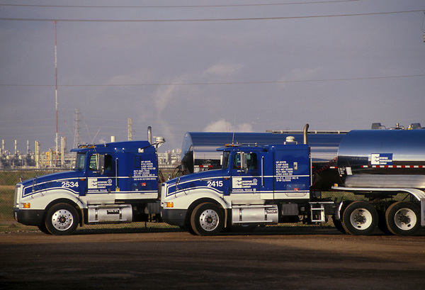Two large blue liquid transport trucks parked beside each other