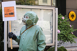 May 13, 2019 - Kyiv, Ukraine - Emigrant activists of the Association of Indigenous Peoples of Russia wearing hazmat suits picket the German Embassy with the demand to audit Russian oil companies that had exported crude oil to EU countries and, activists believe, it had led to an environmental catastrophe in Tatarstan, in Kyiv, Ukraine, May 13, 2019. Russia's Investigative Committee identified six suspects in the contamination of millions of barrels of crude, which shut down pipeline shipments to some European countries. In March and April this year, some of the suspects allegedly supplied oil contaminated with organic chlorides to a pipeline point in Russia's Samara region to hide oil theft, the Committee said, without elaborating on the details of the crime. (Credit Image: © Sergii Kharchenko/ZUMA Wire)