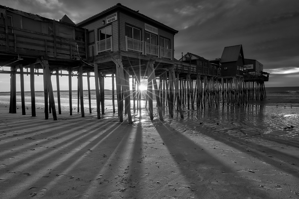 B&amp;W New England photography of a sunrise at Old Orchard Beach and its historic pier near Portland Maine. The sun was just crossed the horizon and created a beautiful sun star and rays. The long shadows of the wood pilings provided great leading lines into the frame. <br />