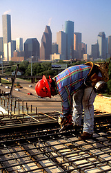 Stock photo of a construction worker preparing steel rebar framework before a concrete pour.