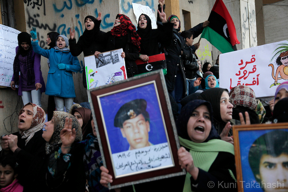 "Protesters against Col. Muammar Gaddafi hold photos in Benghazi, Libya, on Feb 27, 2011, of victims of ""prison massacre"" on June 29, 1996 ordered by Gaddafi. The oppositions against Gaddafi took control of the city early last week..Photo by Kuni Takahashi"