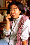 Korean woman age 29 talking on telephone.  St Paul Minnesota USA