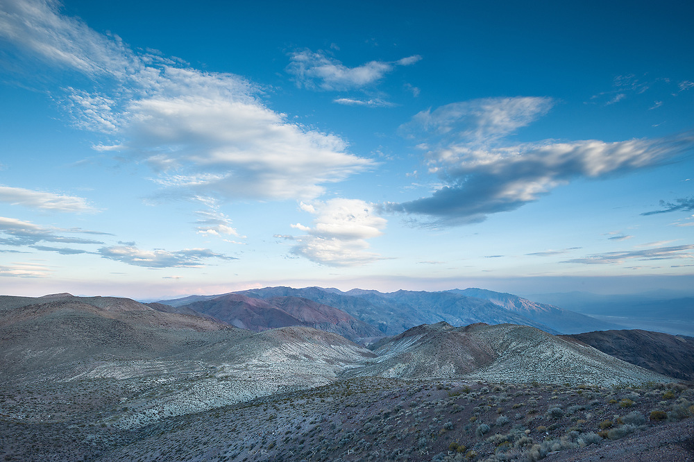 Death Valley, California.  One of the first lessons of photography is to always turn and look at what's in back of what your are shooting, because sometimes the spectacle in front of us also shines light on what's behind us.  One mile in altitude above Badwater Basin, I have come to Dante's View in the Black Mountains, to watch the sun set behind the Panamint Range to the west.  It is a spectacular view point with a precipitous drop, all the way to the salt flats on the floor of Death Valley.  The sun is crouched behind a cloud out there, sending great streaks of light across the jagged peaks, at an angle that still doesn't totally penetrate to the depth of the valley--an image I will share at another time perhaps.  But for now, I remembered to look back,for this view down the Amargosa Range.  Coffin Peak drops more gradually from this side, the flank ridges forming a gunsite of sorts, aiming into the skyline of peaks beyond. The sky seems to literally come at me from this angle, clouds parting to either side of me as though I am unmovable, like water around an island in the stream.  Geologically old, you look out into time here, and after awhile in the quiet, time creeps into my thoughts as well.  As I watch, a spotlight appears on a mountainside down the line. Maybe it symbolizes a path, a route, that I could have done better, could have done different.  I always think so...I wonder how you ever know, really, the best way. The view behind me is always of remembrance, and some things are stripped and barren when I look back.  But memory has many landscapes, and to say mine are all this simple would not be fair.  I look for as long as I dare while waiting for the end of this day, before I turn around again, and face into it.