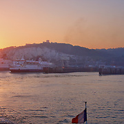 Leaving the Port of Dover at sunset on a French-flagged DFDS ferry, with Dover Castle atop the white cliffs. Two P&O Ferries - the UK flagged competition - get ready to sail.