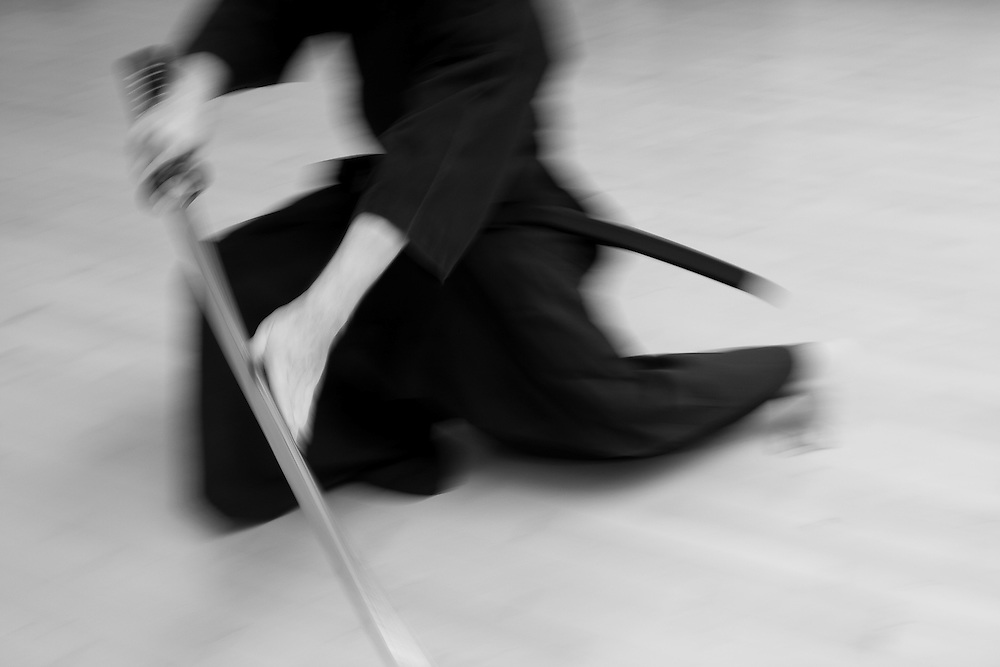 A long exposure blurs the motion as a Iaido teacher demonstrates a kata from the koryu (old style) series