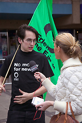 Friends of the Earth supporter holding protest flag and talking to reporter,