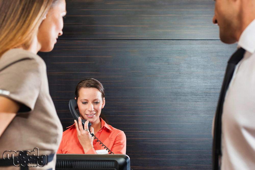 Receptionist calling for her manager while business people waiting in lobby