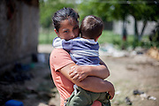 A mother holds her child in the Roma area of Frumusani.