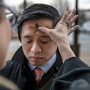 "ALEXANDRIA, VA - MAR1: Pastor Robin Anderson, from  Commonwealth Baptist church, puts ""glitter ashes"" on Diem (he didn't not want to use last name), for Ash Wednesday, outside the Braddock Road metro station, in Alexandria, VA, March 1, 2017. Across the country, churches involved with the advocacy group Parity will be giving out ""glitter ashes"" to demonstrate that LGBT people should be included in Christianity.(Photo by Evelyn Hockstein/For The Washington Post)"