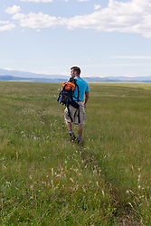 man backpacking in a beautiful grassy field in New Mexico