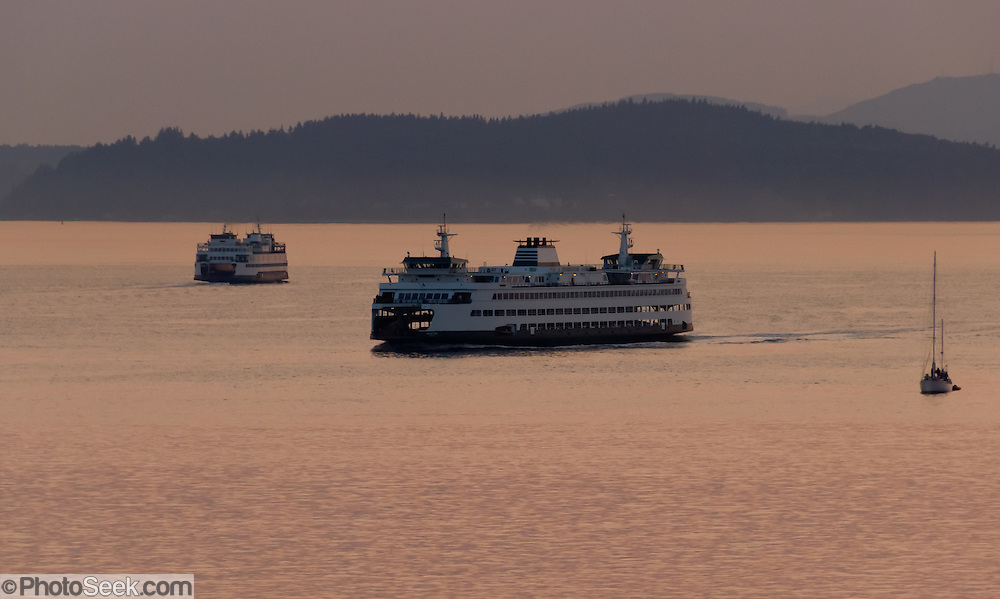 Sunset over Puget Sound and a Washington State Ferry, seen from downtown Seattle, Washington, USA.
