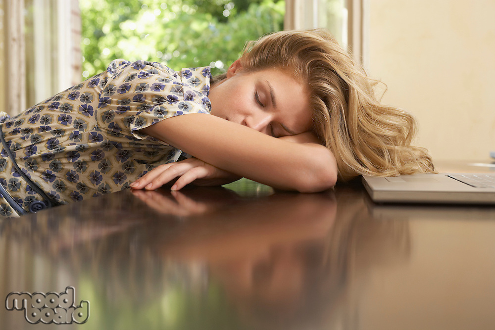 Young woman sleeping in front of laptop in living room