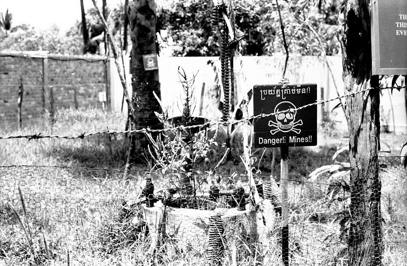 A sign warning for the danger of active landmines in a fenced field outside Siem Reap, Cambodia.