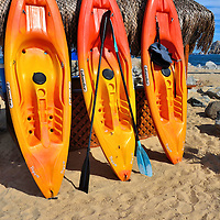 Three Colorful Kayaks Against Beach Umbrella in Cabo San Lucas, Mexico<br /> The vacation formula in Cabo San Lucas is simple: sun, beach, party and repeat until you have to go home.  Everything you need for a good time is available, including these kayaks and the thatched umbrella.  Enjoy!