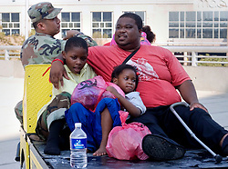 31st August, 2005. 'Hell on earth.' A father and his children are evacuated from The Superdome in New Orleans, Louisiana where over 20,000 refugees from hurricane Katrina are crammed into hellish conditions.