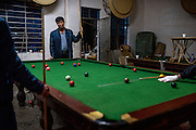 The crew of a sand dredging vessel relax by playing pool at the end of their workday in Simaogangzhen, Yunan, China.
