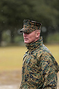 US Marine drill instructor watches recruits fall into formation in a rain storm during bootcamp January 13, 2014 in Parris Island, SC.