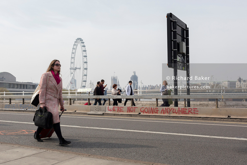 Commuters and visitors walk across the closed Waterloo Bridge on day 4 of protests by climate change environmental activists with pressure group Extinction Rebellion, on18th April 2019, in London, England.