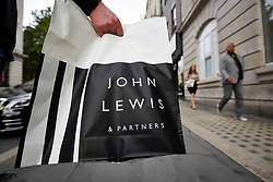 "© Licensed to London News Pictures. 05/09/2018. LONDON, UK. A customer holds a redesigned shopping bag. Rebranding has taken place at the flagship Oxford Street department store of John Lewis.  Now known as ""John Lewis & Partners"", the rebranding puts the group's 83,000 staff, known internally as partners, at the ""heart of the business"" and will take five years to roll out across stores nationwide.  Waitrose will also rebrand to ""Waitrose & Partners"" as the group faces increasing challenges in the high street.  Photo credit: Stephen Chung/LNP"