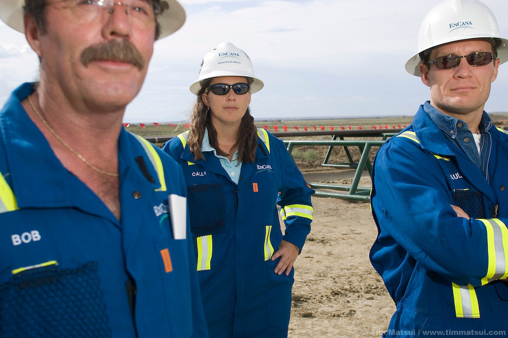 JONAH FIELD, SUBLETTE COUNTY, WY - Bob Williams, left, Cally McKee, center, and Paul Ulrich, right, of Encana at a drilling pad in the Jonah Field, Wy., on August 8, 2005. Encana, BP, and Ultra Petroleum are the main operators in the 30,200 acre field, but Encana is expected to drill two thirds of the wells to yield upwards of 10.5 trillion cubic feet of natural gas which has a current market value of $55 to $60 billion dollars. Encana could make $2 billion in profit per TCF depending price trends and production costs. Jonah Field operators are seeking an 'in-fill' project which will allow for an increase of wells from the currently permitted 533 to 3100 by decreasing well pad spacing from 40 acres to 20 acres and possibly down to 10 acres spacing. This will allow for a greater number of vertical as opposed to directionally drilled wells. Vertical wells take less time, are easier, and therefore cheaper to drill but require a greater amount of surface disturbance. Development and completion, the drilling and hooking up of wells to pipelines, is expected to take 10-15 years while area gas reserves are expected to last 40-60 years. .