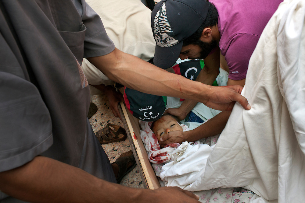A child killed by a Gaddafi's sniper is putted in a coffin in the Gorji area of Tripoli the day after the rebels enter in the Libyan capital.