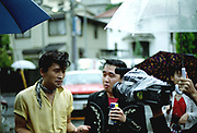 Man with a neckerchief and quiff being filmed in the rain, Japan, 2003