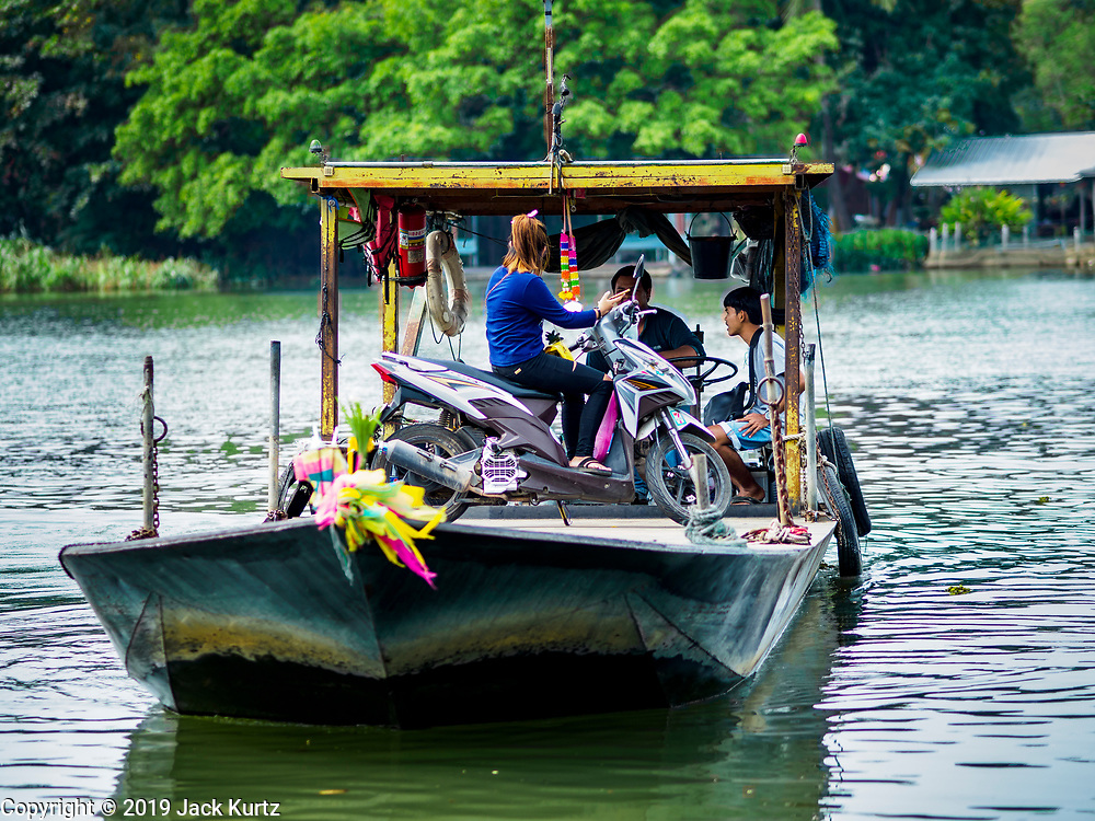 "09 JANUARY 2019 - KANCHANABURI, THAILAND: A small ferry crosses the River Kwai. The ferry goes across the River Kwai downriver from downtown Kanchanaburi, the site of the famous ""Bridge on the River Kwai."" Small ferries like this, once common on Thai river crossings, are disappearing because Thailand has dramatically improved its infrastructure since this ferry started operating about 50 years ago. The ferry operator said his grandfather started the ferry, with a small raft he would pole across the river, in the late 1960s. Now his family has a metal boat with an inboard engine. There are large vehicle bridges across the river about 5 miles north and south of this ferry crossing, but for people in rural communities on the west side of the river the ferry is still the most convenient way to cross the river.      PHOTO BY JACK KURTZ"