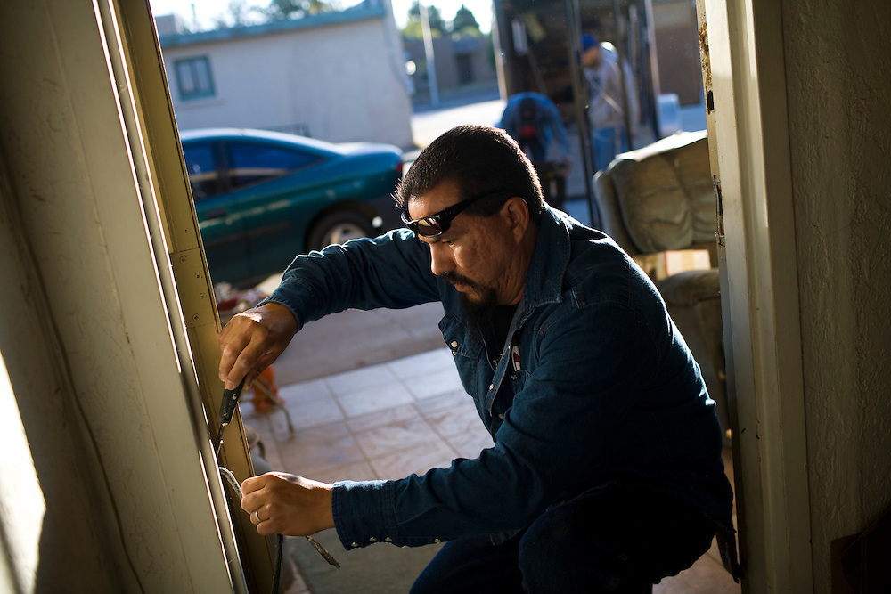 Joe Tarango weatherizes a door.  He works for the Community Action Agency(CAA). The CAA received stimulus funding and, among other things, works on weatherizing the homes of poor families and individuals in New Mexico.