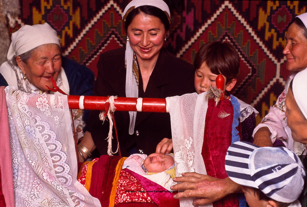 "Besikke Salu, or ""Putting in the Cradle,"" is a ceremony for blessing a new baby.  This entails placing the infant in its cradle and, to ensure blessings, putting a small mirror or brush under the pillow for a baby girl or a whip and knife for a boy.  A burning sprig of sage or a flame, as pictured here, is passed over the cradle as a symbol of cleansing, life and protection.  A grandmother then pinches the baby's nose to make it cry, which assures a calm, deep sleep afterwards.  Arailym Sametova is the baby being blessed here.  Her mother, Gulmarzhan Ikhanova, is at left, and the Godmother, Galiya Usenbaeva, is the young woman behind the cradle."