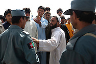 Afghan National Police restrain spectators at the site of a bomb blast in Kabul August 18, 2009. Seven people were killed and 52 wounded by a suicide car bomber who rammed his car into a convoy of Western troops in the Afghan capital on Tuesday, said Farid Raeed an official at the public health ministry. The strike, on the road heading east out of the capital toward the city of Jalalabad, comes two days before a tense presidential election. Photo by Keith Bedford