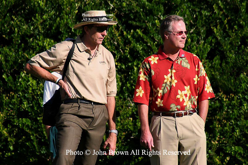 David Ledbetter, (in straw hat) fifteen year old Michelle Wie's swing coach, and the Golf Channel's Mark Rolfing (wearing red aloha shirt) observe Ms. Wie during a practice round prior to The 2005 Sony Open In Hawaii. The event was held at The Waialae Country Club in Honolulu.
