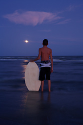 Boy standing on Galveston beach at night with his skimboard