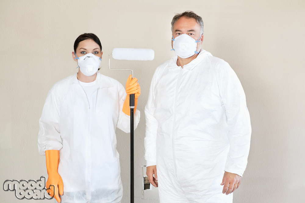Portrait of female worker holding paint roller with man standing with her