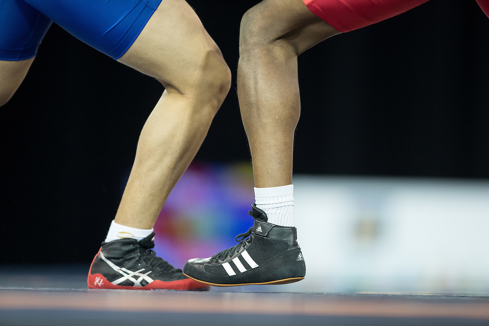 The feet of Querys Perez of Venezuela (in blue) and Cristian Mosquera of Colombia are seen during their semi-final bout in the 85kg class of the men's greco-roman wrestling  at the 2015 Pan American Games in Toronto, Canada, July 15,  2015.  AFP PHOTO/GEOFF ROBINS
