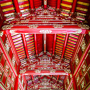 An ornate red ceiling in a restored building at the Imperial City in Hue, Vietnam. A self-enclosed and fortified palace, the complex includes the Purple Forbidden City, which was the inner sanctum of the imperial household, as well as temples, courtyards, gardens, and other buildings. Much of the Imperial City was damaged or destroyed during the Vietnam War. It is now designated as a UNESCO World Heritage site.