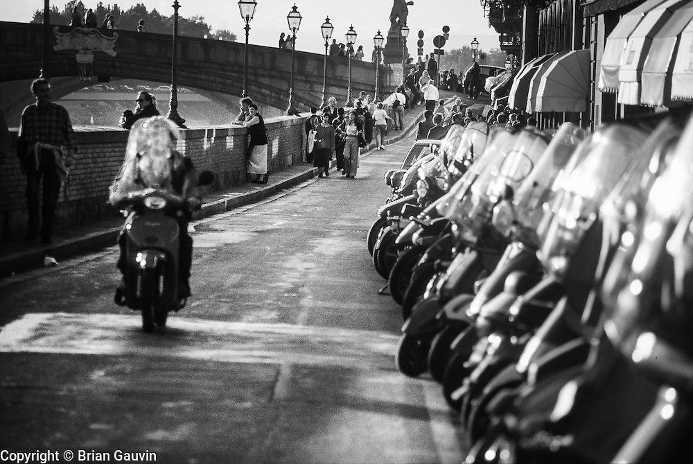 Street lining the Arno River in Florence, Italy. City of scooters